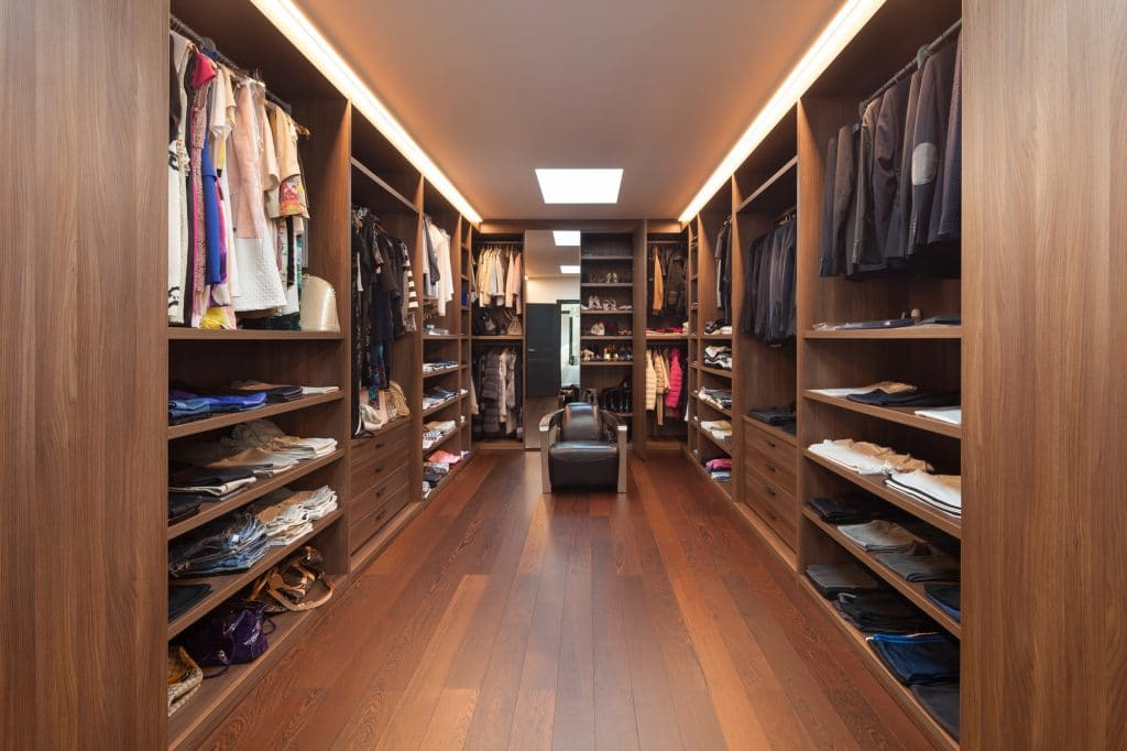 Brown closet with bench and fully organized wardrobe and custom lighting