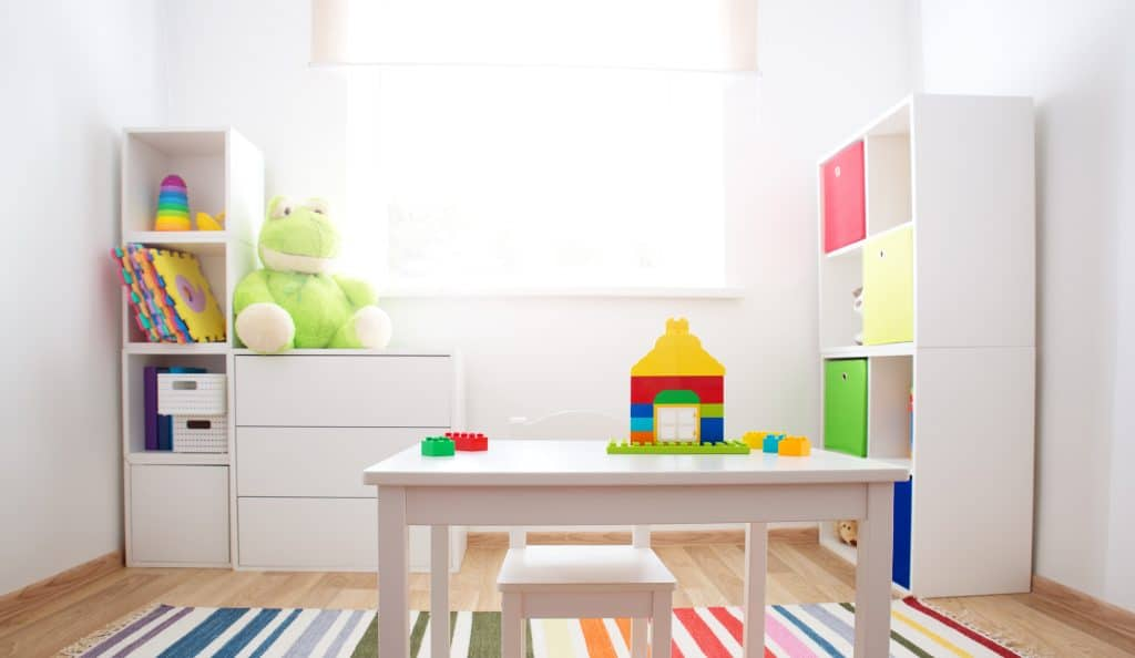 Organized Colourful children room with white walls and furniture. Rainbow carpet at home interior with a window