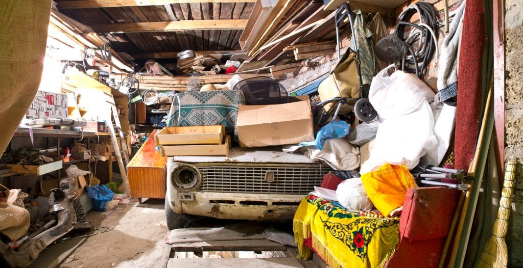 Unorganized Garage inside. Old broken car, shelves with tools and stacks of things.