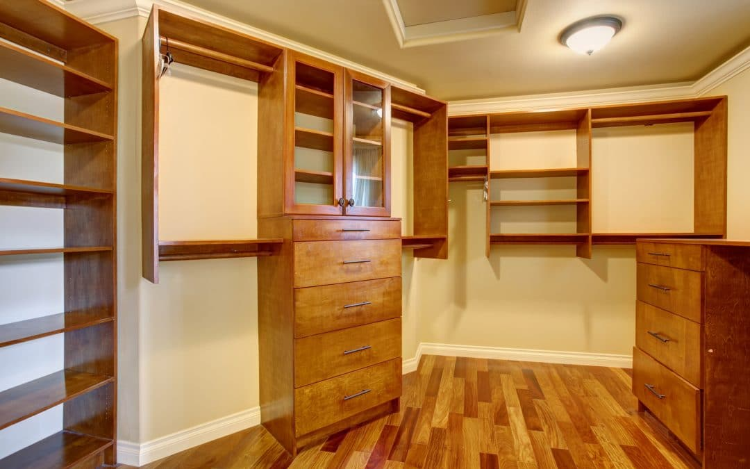 Large walk in closet with hardwood floor, also including many shelves and drawers.
