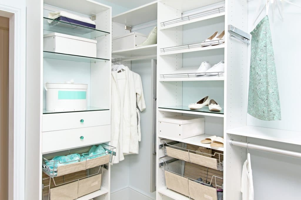 Detail of large walk in closet with modern wardrobe on hangers that are placed on custom shelving and drawers