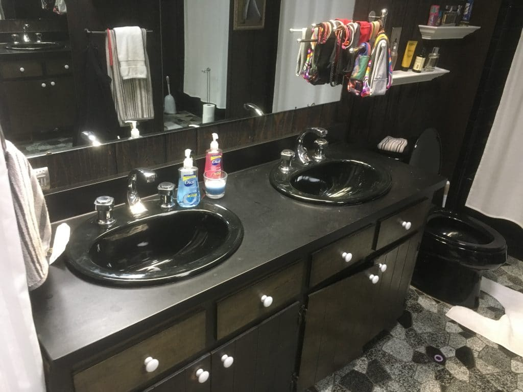 before photo of a dated bathroom vanity with two sinks