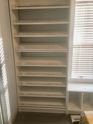 white shoe shelving with chrome stops on shelves to keep shoes from falling into closet floor